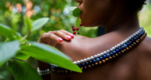 "<img src=""IMG_9902.JPG"" alt=""African American female model standing topless behind green leaves hanging from a tree with berries in her mouth and three Natural Stone Necklaces draped over her back"">"