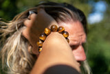 Alt= Male wearing tigers eye beads