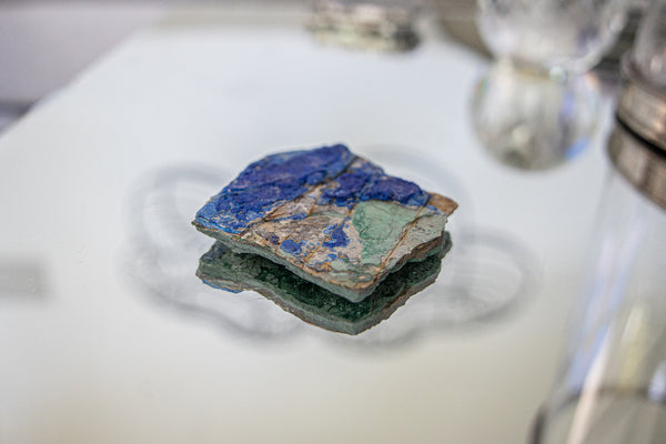 Malachite and Azurite Gemstone Cluster sitting on glass table.