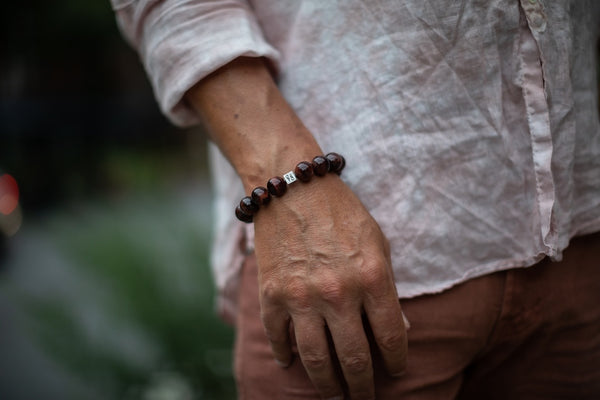 Alt= Male model wearing redtigers eye 14mmm sterling silver cube bracelet.
