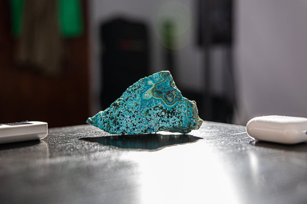 Malachite and Chrysocolla Geode Cluster sitting on desk.