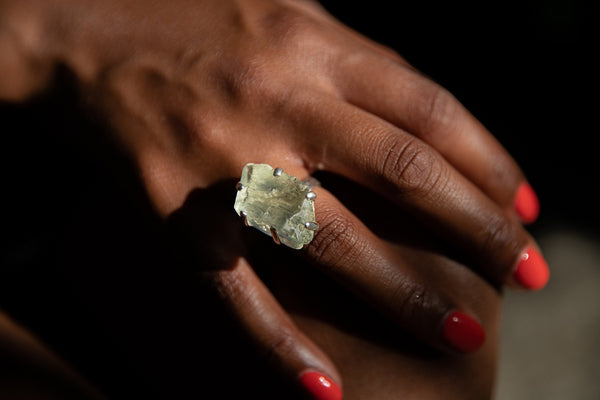 Alt= Model wearing green hiddenite ring on bare hand.