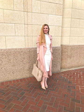 Woman standing with white dress and blush long trench coat
