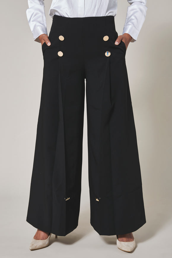 Skinny to Wide Leg Black, Convertible, High-Waisted Pants with 2 rows of 2 gold buttons. Model facing forward with pants in wide leg position.