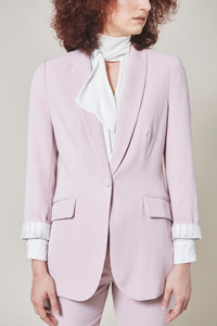 Rosé Colored blazer with pockets and one front button. Model facing forward.