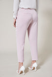 Light pink cigarette pants. Model facing backward.