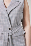Slate grey plaid suit vest close up with detail of front, black button and waist tie.