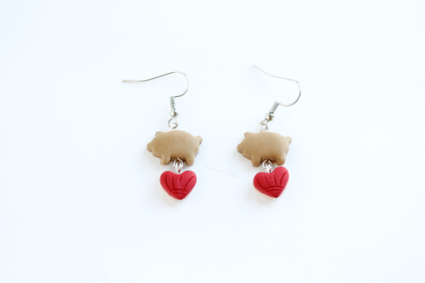 Handmade miniature cochinito earrings with red heart shaped conchas dangling from under the puerquito. White background