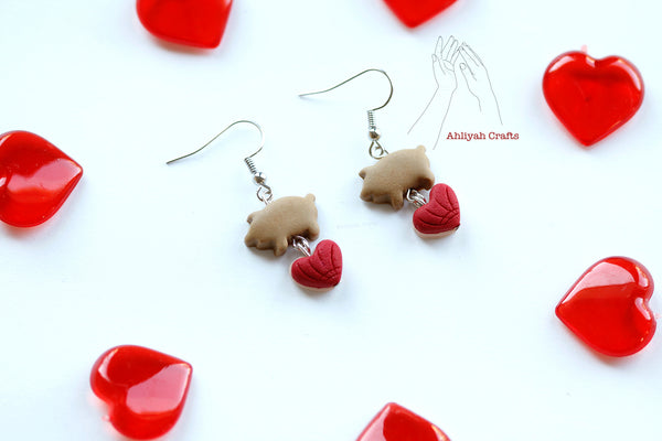 handmade puerquito earrings with red heart shaped concha dangling from the bottom of puerquito. Heart shaped decor surrounds it.