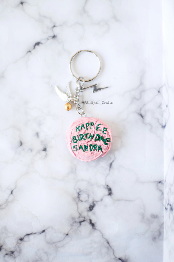 "handmade chocolate harry potter cake with pink icing and green text. Happee Birthdae Harry. Customized name ""Sandra"" Keychain with snitch and lighting bold charms."