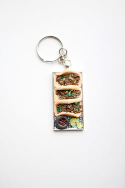 3 carde asada handmade tacos on silver platter keychain. Onions and Cilantro in the tacos. Mini molcajete with salsa roja or verde. Sliced limes.