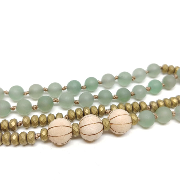"Detail of Palm Canyon Necklace, 33"" mala-style knotted necklace, aventurine, hematite and sandal wood, brass oval pendant"