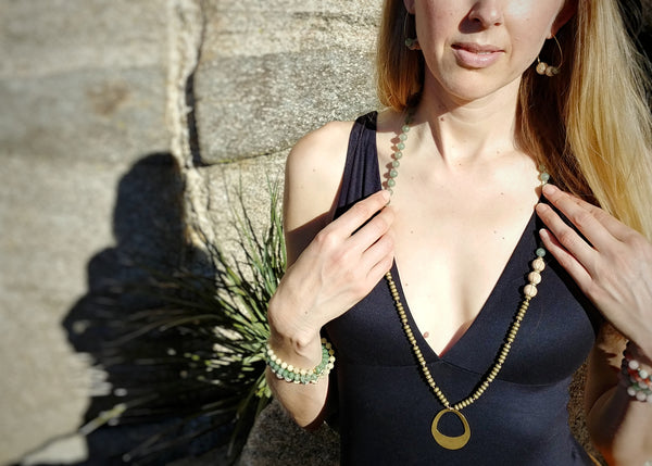 "Model wearing Palm Canyon Necklace, 33"" mala-style knotted necklace, aventurine, hematite and sandal wood, brass oval pendant"