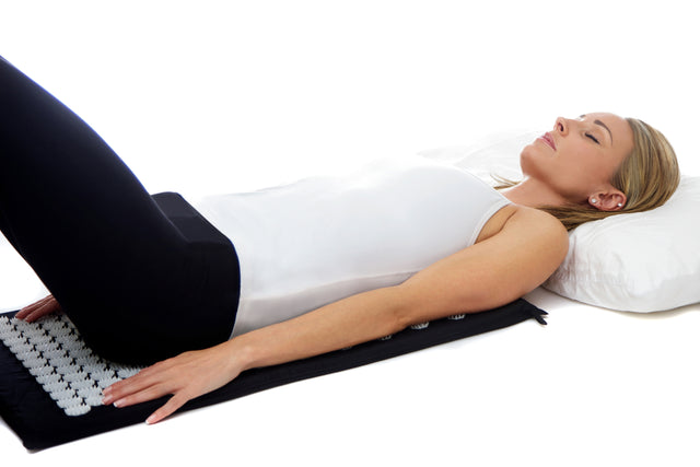 Acupressure mat. Woman lying down on the Chi-mat acupressure mat.