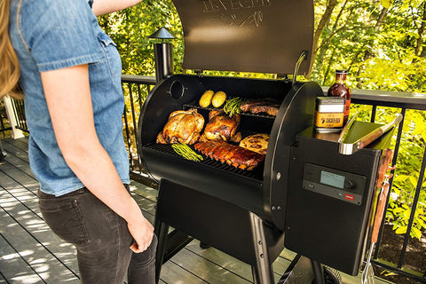 Traeger grill with meats and corn inside