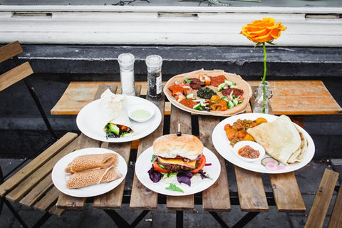 five white plates with food on a wooden outdoor table