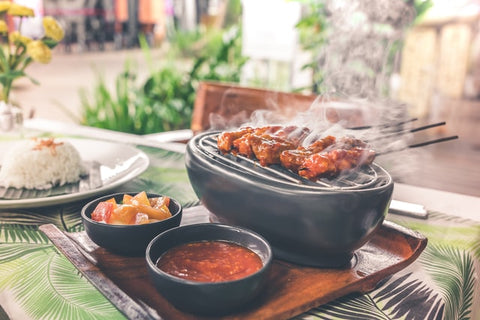 grilled meat on table beside rice and condiments