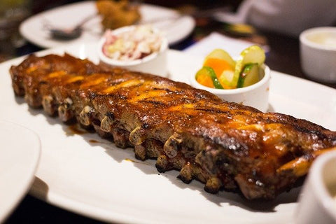 ribs served with the sides on a white plate