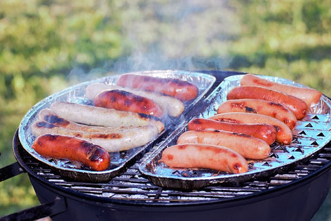 sausages being cooked on an outdoor grill