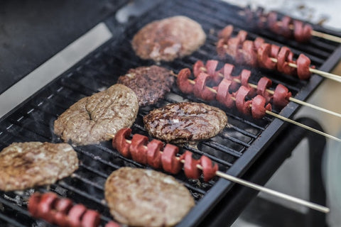 steak and skewered sausages on grill