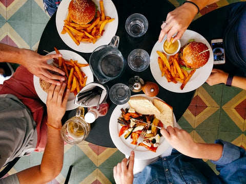 top view of four people eating burgers and fries