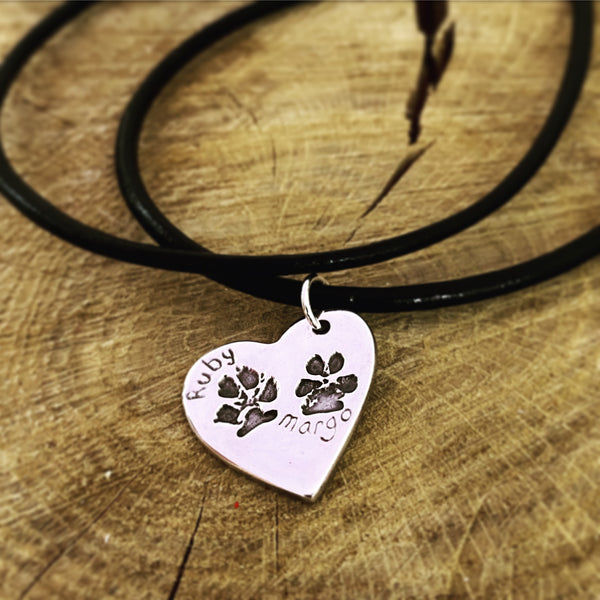 double paw print on a leather necklace