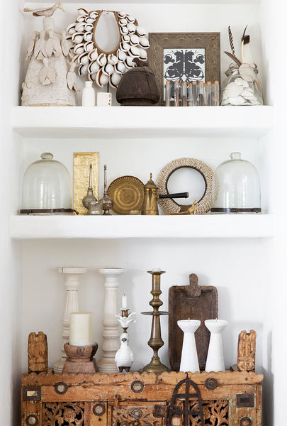 recessed bookshelf with designer metallic and bohemian objects