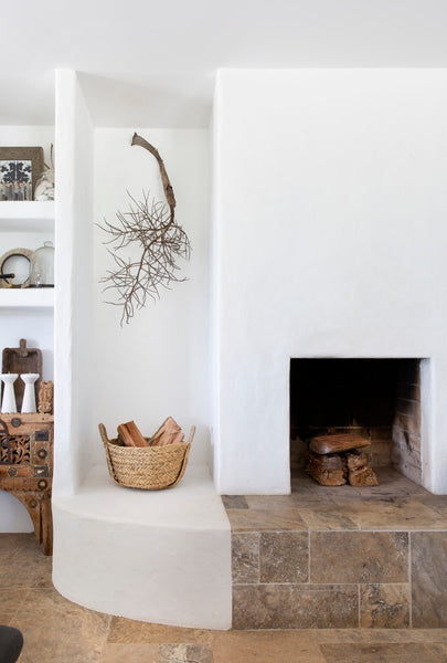 fireplace on stone hearth with wood in basket
