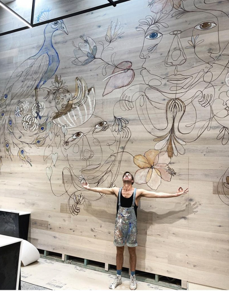 man in front of wall mural featuring line art with figures and peacock