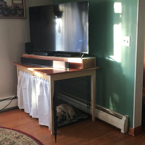 photo of a dog crate under a table with a white curtain blocking the front of the crate with a television and sound bar on top of the table. A fawn pug is laying down inside of the dog crate.