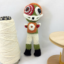 Small amigurumi football player doll next to a spinning wheel spool and a cone of yarn