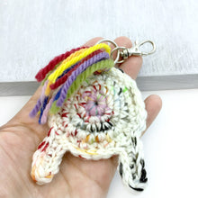 crocheted unicorn butt keychain held in a hand