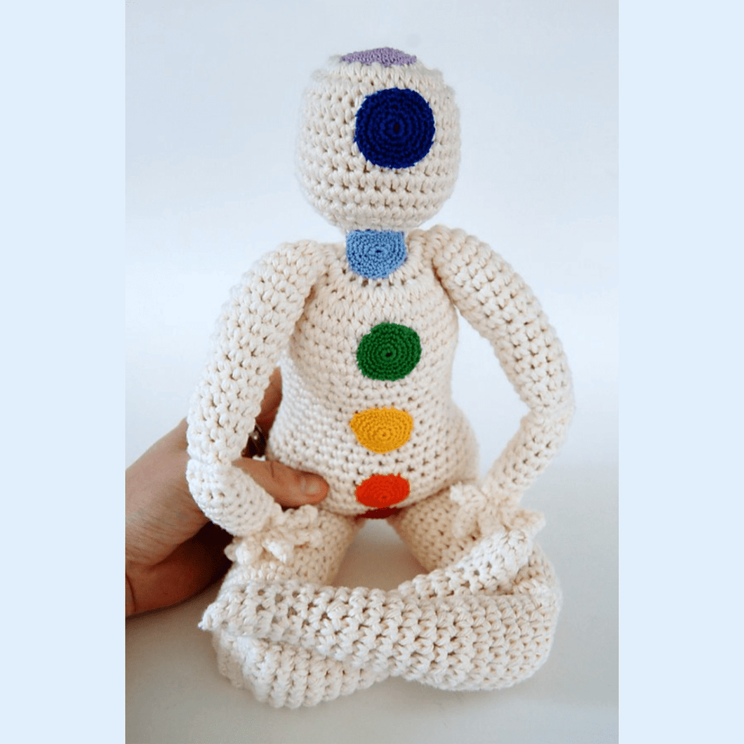Crocheted doll with rainbow Chakra points being held in a hand