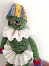 Green amigurumi monster doll wearing a white tutu and frilly collar and a striped hat close up
