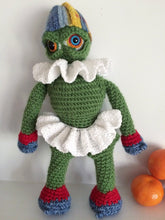 Green amigurumi monster doll wearing a white tutu and frilly collar and a striped hat next to oranges