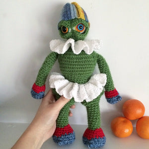 Green amigurumi monster doll wearing a white tutu and frilly collar and a striped hat being held by a hand next to oranges