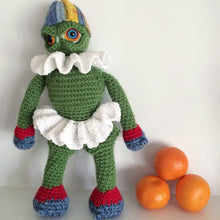 Green plush monster doll wearing a white tutu and frilly collar and a striped hat standing next to oranges