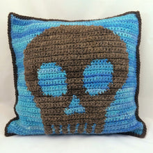 Blue pillow with a gray border and gray skull in the center
