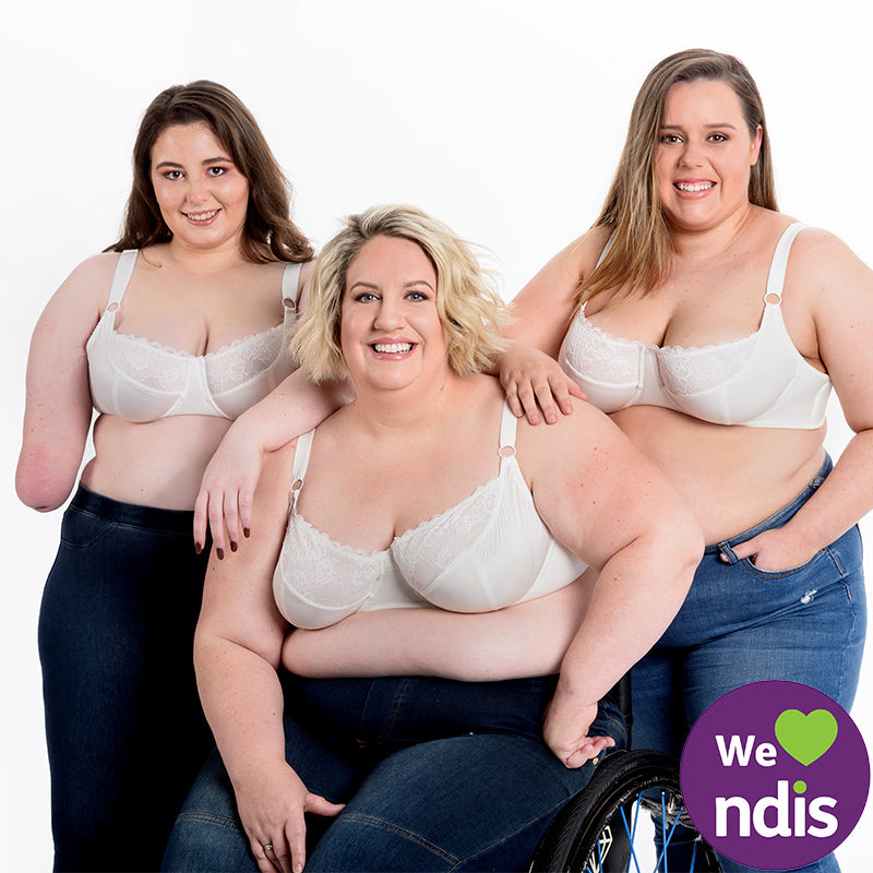 One women with one hand, one women in a wheel chair and one women standing behind.  All wearing a white bra. NDIS logo in the picture.