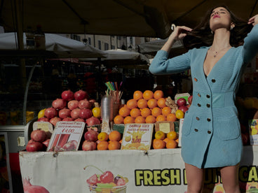 Woman wearing a dress and basking in the sun in front of a fruit stand