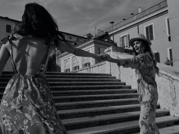 Two woman holding hands with outstretched arms in front a staircase in Italy