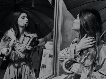Woman in a trench coat holding an umbrella staring at her reflection within a mirror