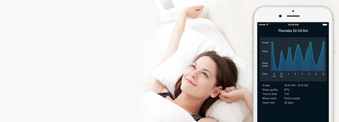 woman lying in bed with Sleep Cycle phone app
