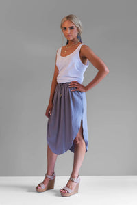 The beautiful Katie skirt is a mid length skirt featuring an elastic waist with ties. It's asymmetrical sides and light cotton linen fabric makes it easy to wear.