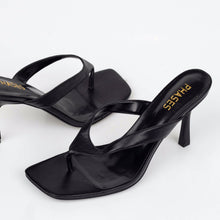 Load image into Gallery viewer, Close up of black flip-flop heels with gold logo