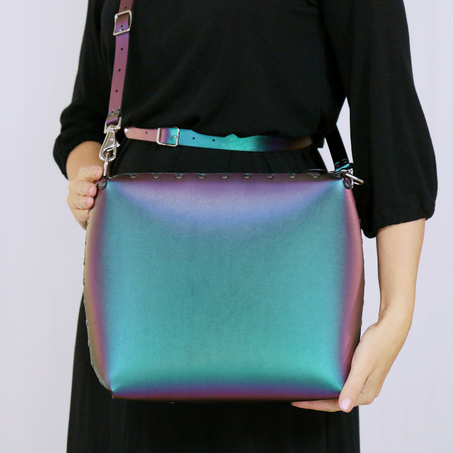 Model holding large chameleon crossbody bag