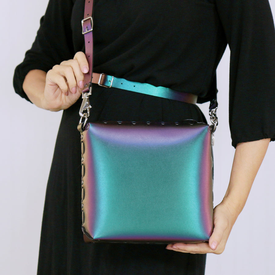 Model holding chameleon medium crossbody bag