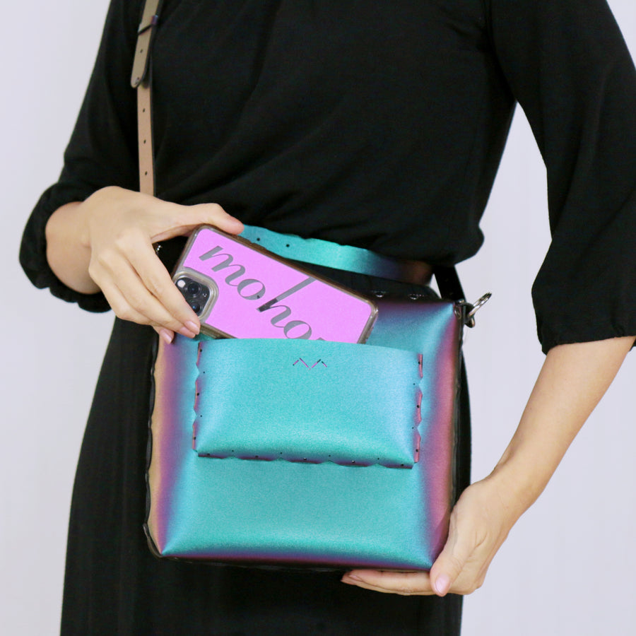 Model putting phone in outside pocket of chameleon medium crossbody bag