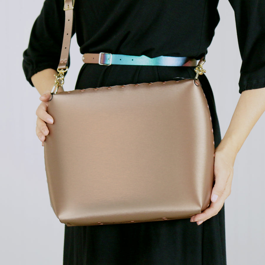 Model holding large mocha crossbody bag