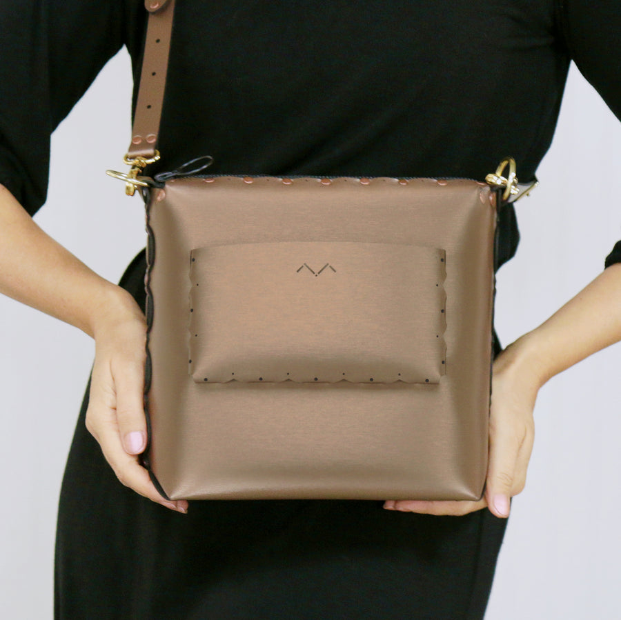 Model showcasing outside pocket of mocha medium crossbody bag